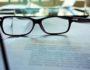 Ein Bild, das Brille, Arbeitsvertrag, Arbeitgeber, drinnen, sitzend enthält.