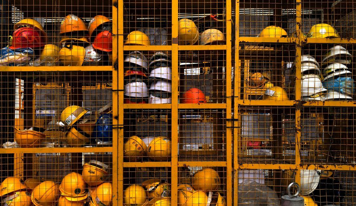 Ein Bild, das drinnen, Regal, gefüllt mit Schutzhelmen enthält. Sicherheit am Arbeitsplatz
